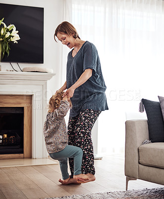 Buy stock photo Full length shot of an attractive young mother and dancing with her daughter in the living room at home