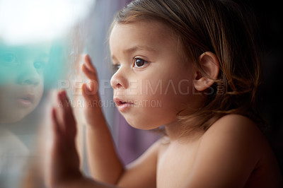 Buy stock photo Cropped shot of an adorable little girl looking outside the window at home