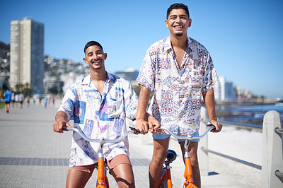 Buy stock photo Cropped portrait of a young gay couple bonding together and riding bicycles along the promenade during a day out