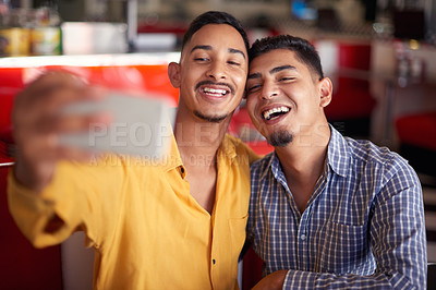Buy stock photo Cropped shot of a young gay couple sitting together and using their cellphones to take a selfie during a date