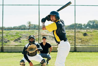 Buy stock photo Cropped shot of a handsome young baseball player preparing to bat a ball during match on the field