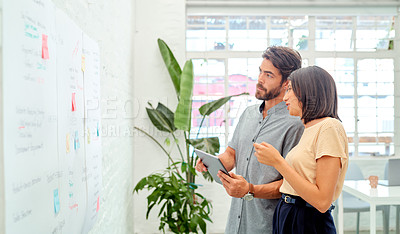 Buy stock photo Shot of two businesspeople using a digital tablet while brainstorming with notes on a wall in an office