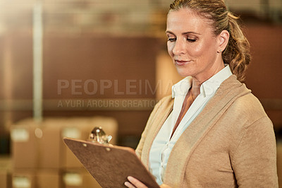 Buy stock photo Cropped shot of an attractive mature supervisor standing alone in a warehouse and using a clipboard for stocktaking
