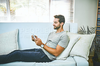 Buy stock photo Cropped shot of a man using a digital tablet while relaxing on the sofa at home