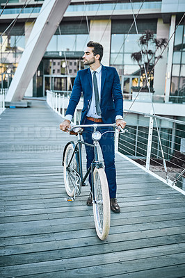 Buy stock photo Shot of a well-dressed businessman traveling through the city with his bicycle