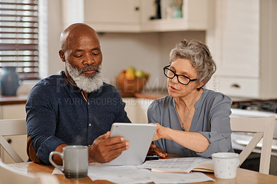 Buy stock photo Cropped shot of a senior couple using a digital tablet while going over bills and paperwork together at home