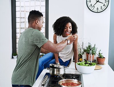 Buy stock photo Cropped shot of a man having his wife taste the food that he's preparing