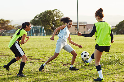 Buy stock photo Full length shot of a young female soccer player dribbling past her opponents during a match outdoors on the field