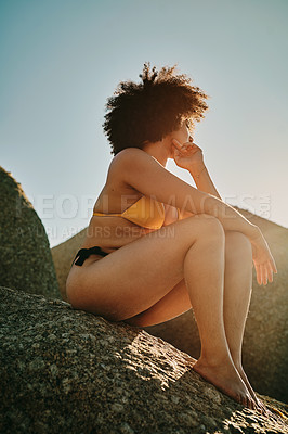 Buy stock photo Full length shot of an unrecognizable woman sitting on a rock and posing during a day out at the beach