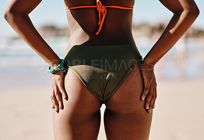 Buy stock photo Cropped shot of an unrecognizable woman standing alone in her bikini during a day out on the beach