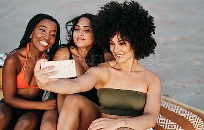 Buy stock photo Shot of three friends taking a selfie while spending the day at the beach