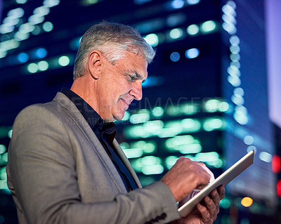Buy stock photo Cropped shot of a mature businessman using a digital tablet outdoors in the evening with the cityscape in the background