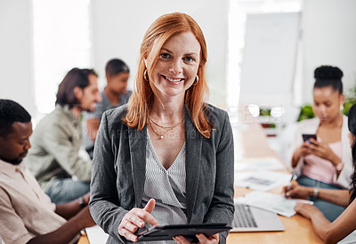 Buy stock photo Portrait of a mature businesswoman using a digital tablet in an office with her colleagues in the background