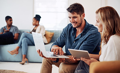 Buy stock photo Cropped shot of a young group of businesspeople sitting in the office together and working wth technology