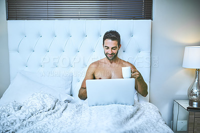 Buy stock photo Cropped shot of a handsome young man drinking coffee and using his laptop while sitting in bed at home