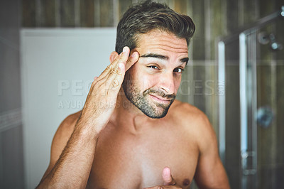 Buy stock photo Portrait of a handsome young man examining his face and skin tone inside his bathroom at home