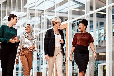 Buy stock photo Shot of a group of businesswomen walking alongside each other in an office