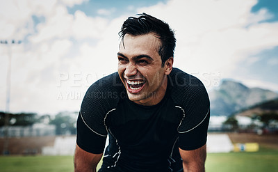 Buy stock photo Cropped shot of a handsome young man smiling while taking a break on the field during the day