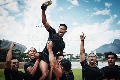 Buy stock photo Cropped shot of a handsome young rugby player holding up a trophy while celebrating with his team on the field