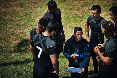 Buy stock photo Cropped shot of a handsome young rugby coach addressing his team on the field during the day