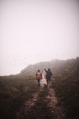 Buy stock photo Shot of two friends and a dog out hiking in the mountains on a foggy day