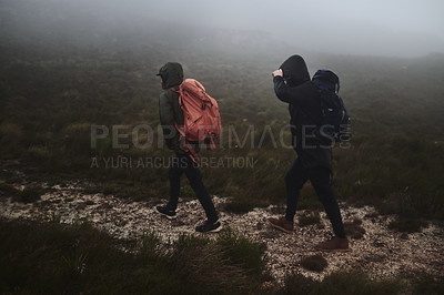 Buy stock photo Shot of two male friends out for a hike on a misty day