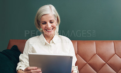 Buy stock photo Cropped shot of an attractive mature woman sitting alone on her sofa and using her tablet at home