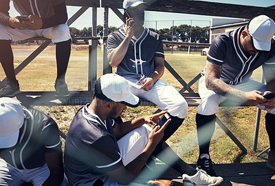 Buy stock photo Shot of a young man using a smartphone at a baseball game surrounded by his team mates