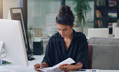 Buy stock photo Cropped shot of an attractive young businesswoman working on paperwork in her office