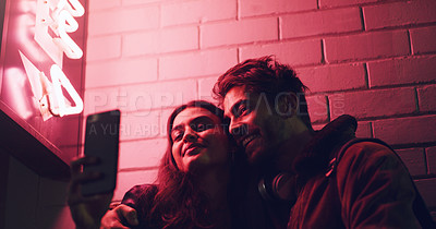 Buy stock photo Shot of a young couple taking a selfie while standing outside a building at night