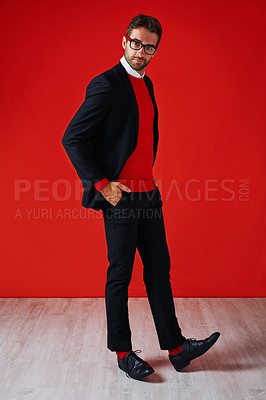 Buy stock photo Studio portrait of a handsome and stylish young man posing with his hands in his pockets against a red background