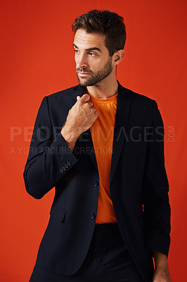 Buy stock photo Studio shot of a handsome and stylish young man looking thoughtful against a red background