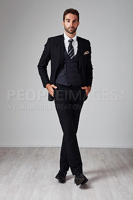 Buy stock photo Studio portrait of a handsome and stylish young man posing with his hands in his pockets against a grey background