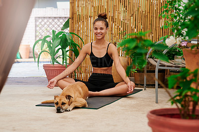 Buy stock photo Shot of a young woman doing yoga with her dog in front of her at home