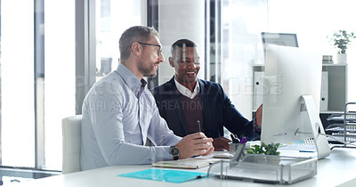 Buy stock photo Shot of two businessmen working together on a computer in an office