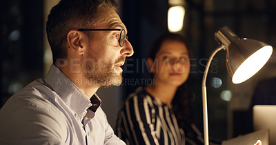 Buy stock photo Shot of a mature businessman having a meeting with his colleagues in an office at night