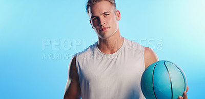 Buy stock photo Studio portrait of a handsome young male basketball player posing with a ball against a blue background