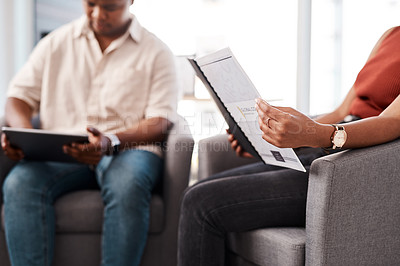 Buy stock photo Closeup shot of an unrecognisable businesswoman reading a folder while sitting on a couch in an office with a colleague in the background