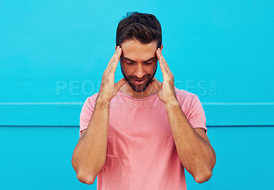 Buy stock photo Shot of a handsome young man looking stressed against a blue wall