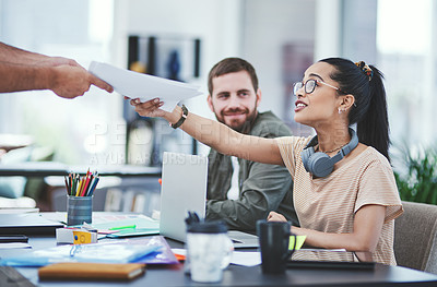Buy stock photo Shot of a group of designers passing paperwork to each other during a meeting in an office