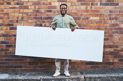 Buy stock photo Shot of a young man holding a blank banner against an urban background outdoors
