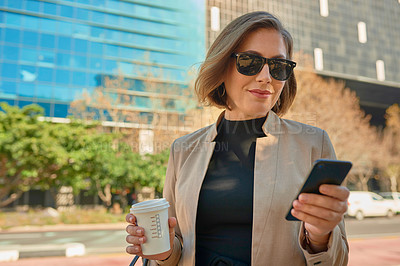 Buy stock photo Shot of a businesswoman using her cellphone while out in the city with a coffee