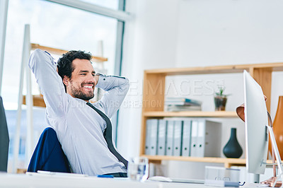 Buy stock photo Shot of a young businessman taking a break at his office desk