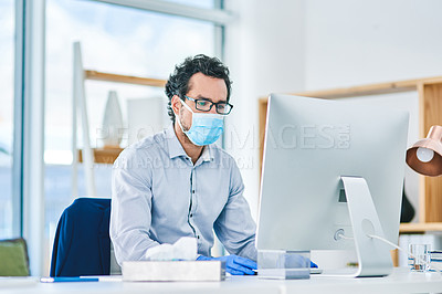 Buy stock photo Shot of a young businessman wearing a mask and gloves while working on a computer in an office