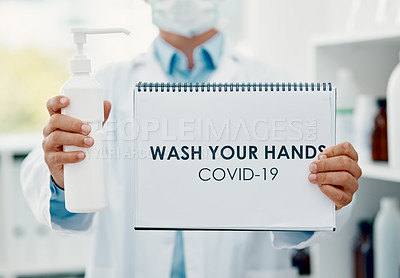 "Buy stock photo Shot of a scientist holding a sign with ""wash your hands"" on it and hand sanitiser in a laboratory"