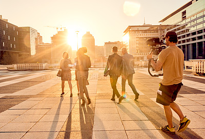 Buy stock photo Shot of a group of businesspeople being filmed while walking through the city