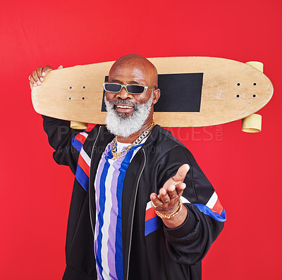 Buy stock photo Shot of a mature man holding a skateboard against a red background