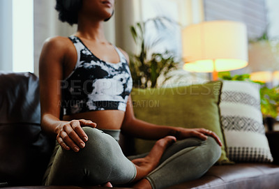 Buy stock photo Closeup shot of an unrecognisable woman sitting in lotus position while practising yoga at home