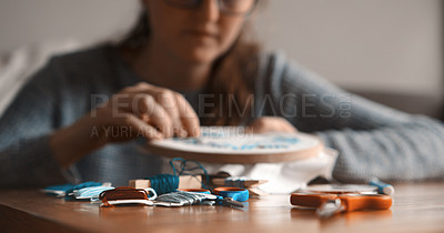 Buy stock photo Cropped shot of a young woman doing embroidery while relaxing at home