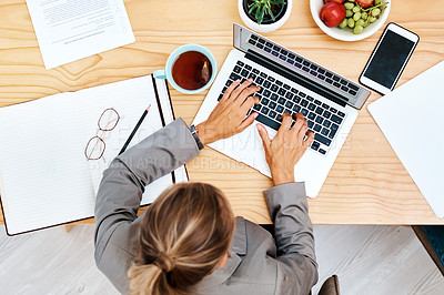 Buy stock photo High angle shot of a young businesswoman working on a laptop in an office